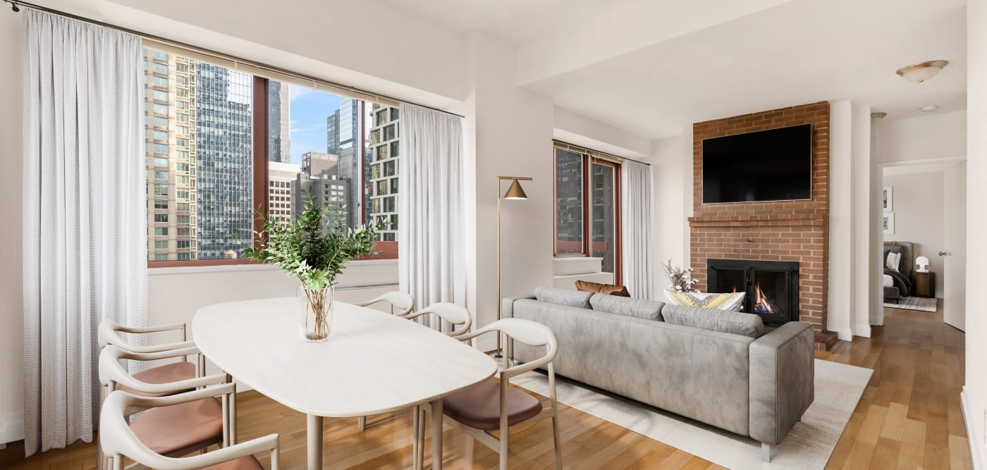 Spacious living room with a gas-burning fireplace and a view at The Ellington in New York, New York