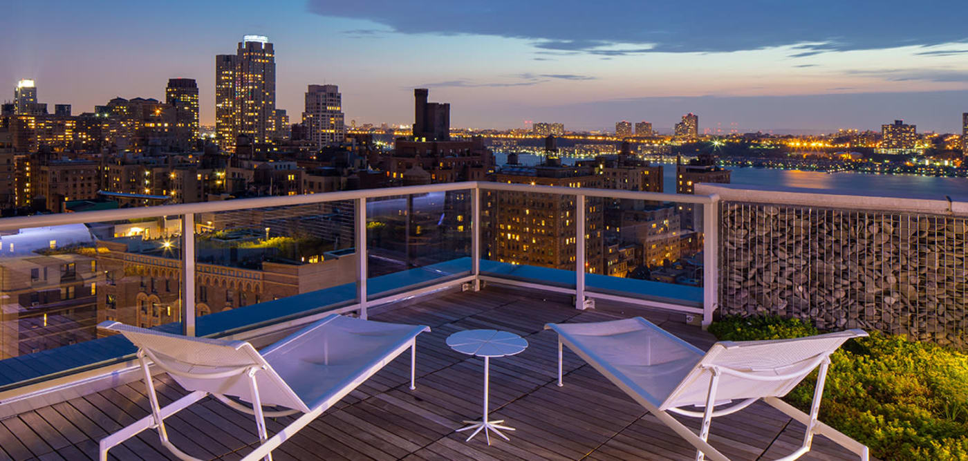 Roof top lounge at dusk with a beautiful view of the city at The Larstrand in New York, New York