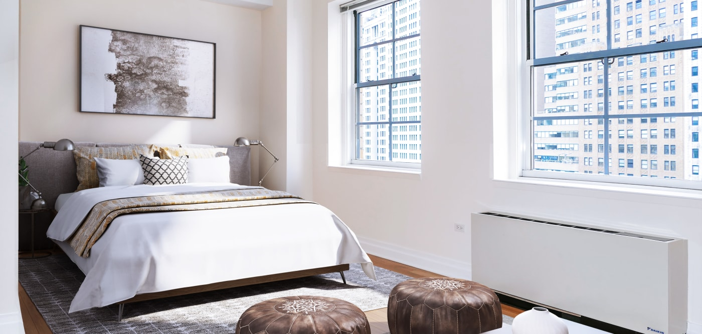 Large main bedroom with two large windows for a city view at 21 West Street in New York, New York
