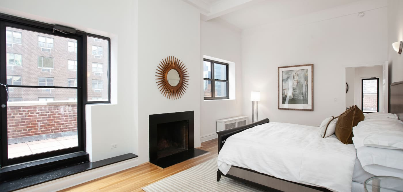 Main bedroom with patio access at The Sutton Collection in New York, New York
