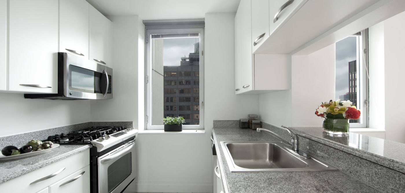 A kitchen with a stainless-steel microwave at The Metropolis in New York, New York
