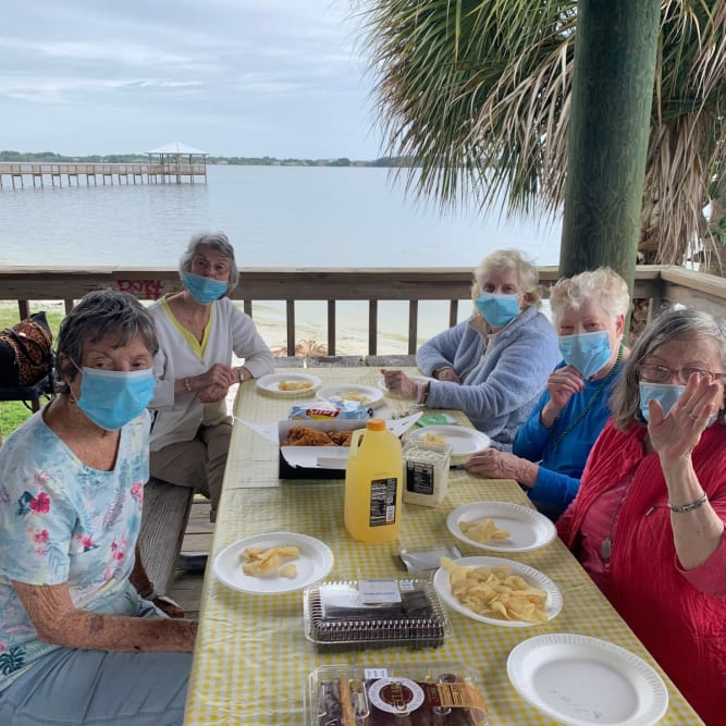 residents enjoying a meal by the water