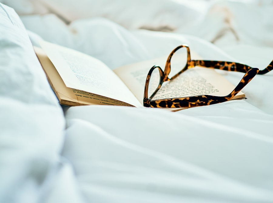 A book and some reading glasses sitting on a bedcover at The Meridian at Waterways in Fort Lauderdale, Florida