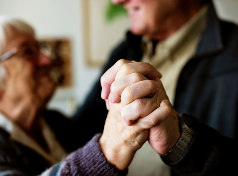 Two residents holding hands at The Meridian at Boca Raton in Boca Raton, Florida