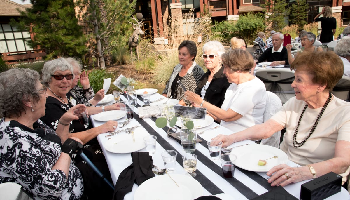 Residents eating at an outdoor dining table at Touchmark on Saddle Drive in Helena, Montana