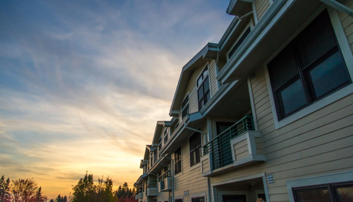 An apartment building exterior at dusk at Touchmark at Fairway Village in Vancouver, Washington