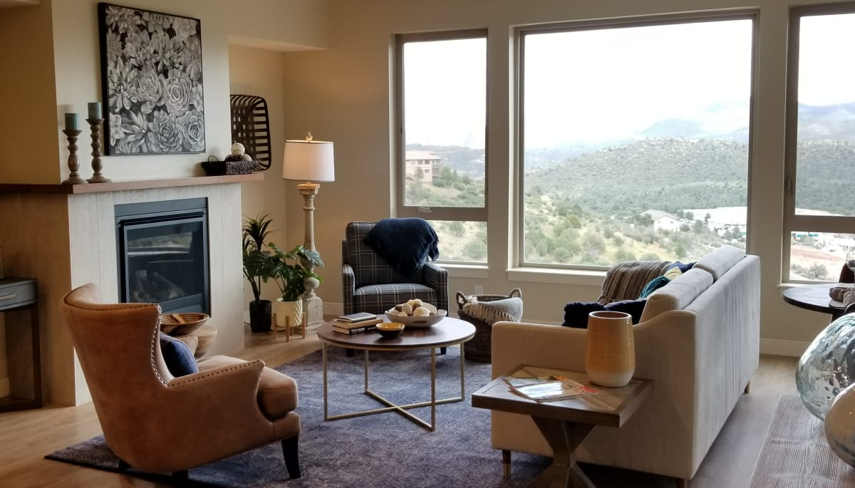 Seating in an apartment living room with large windows at Touchmark at The Ranch in Prescott, Arizona