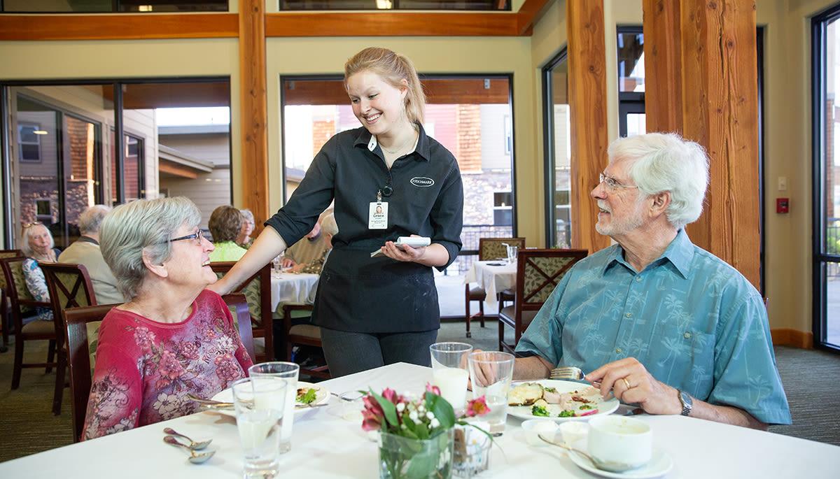 two senior residents talking with their waitress