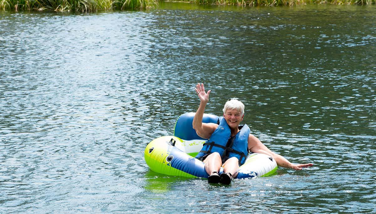 senior woman floating on an inner tube in the lake
