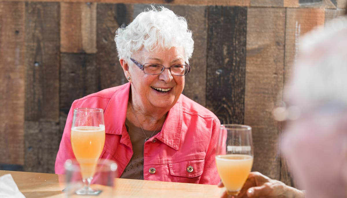Resident laughing at outdoor brunch at Touchmark at Wedgewood in Edmonton, Alberta