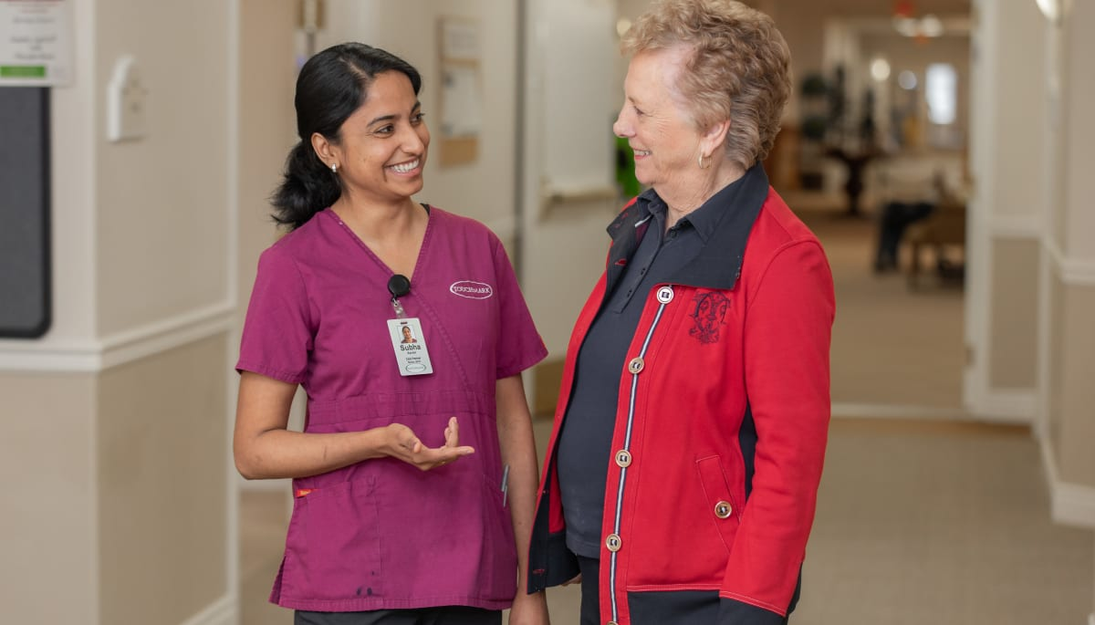 Caregiver and resident in hallway at Touchmark at Wedgewood in Edmonton, Alberta