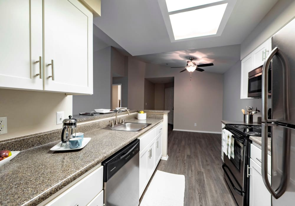 White Renovation Kitchen with Stainless steel appliances at Sierra Del Oro Apartments in Corona,CA