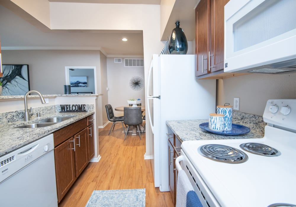 A bright kitchen with granite countertops and white appliances at Estates on Frankford in Dallas, Texas