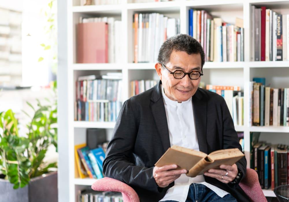 Resident reading a book at Inglenook At Brighton in Brighton, Colorado