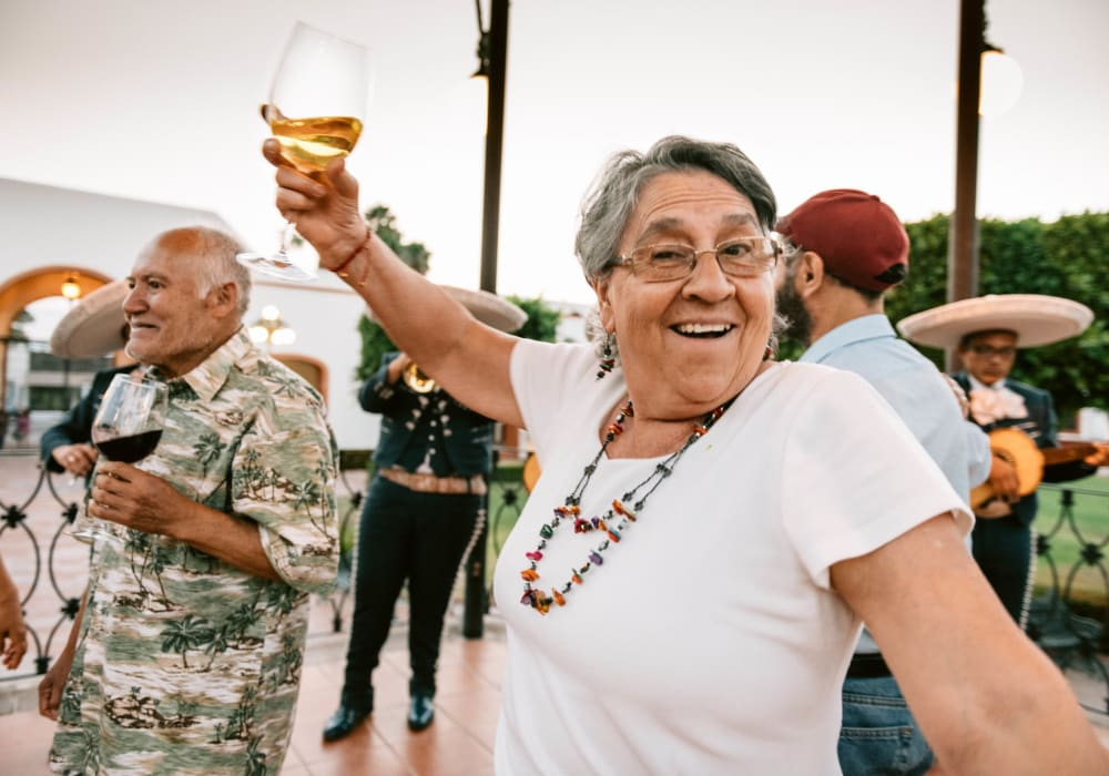 Woman dancing with a drink and a smile in Rising Sun, Maryland near Fairview Senior Apartments