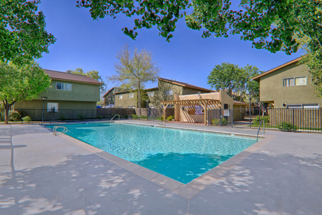 Beautiful sparkling swimming pool on a sunny day at Woodlands West Apartment Homes in Lancaster, CA