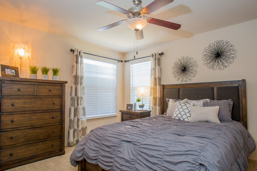 Bedroom with a ceiling fan at Nickel Creek Apartments in Tulsa, Oklahoma