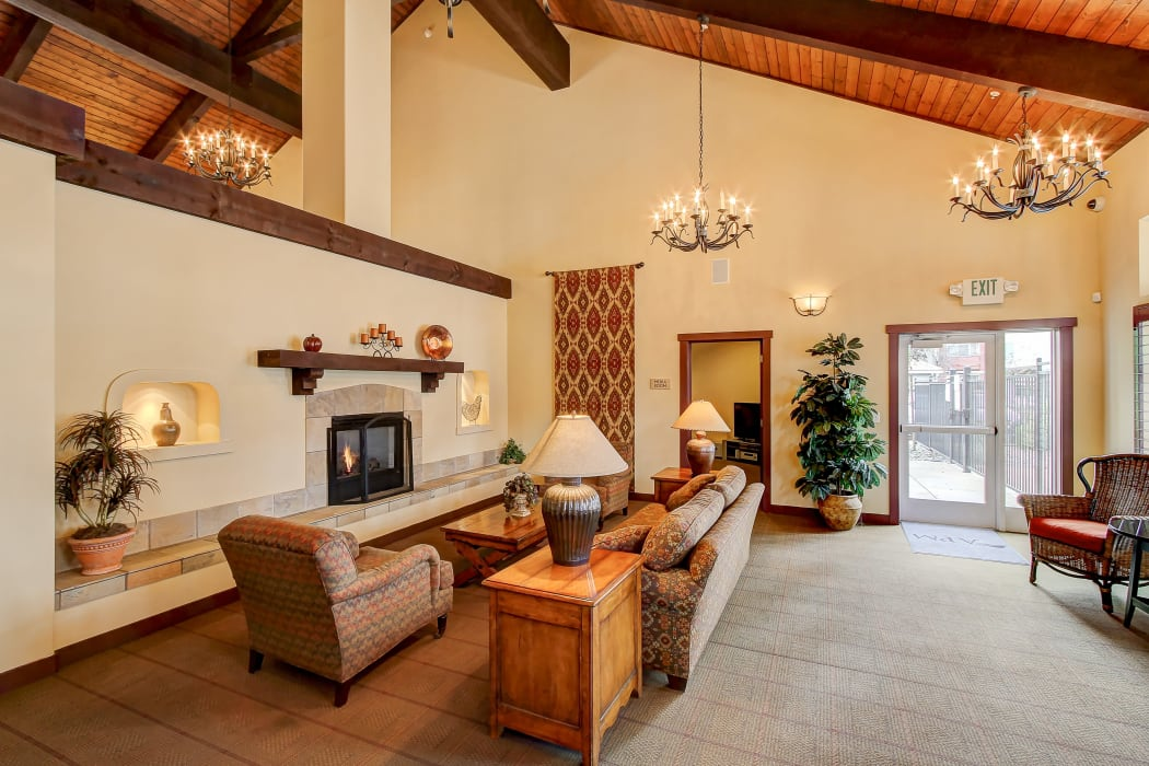 Lounge seating in front of the fireplace in the resident clubhouse at Eaglewood Apartments in Woodland, California