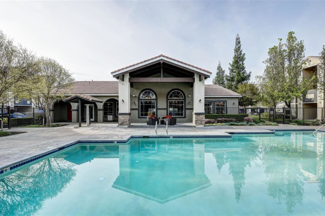 View of the clubhouse from across the pool at Sierra Oaks Apartments in Turlock, California