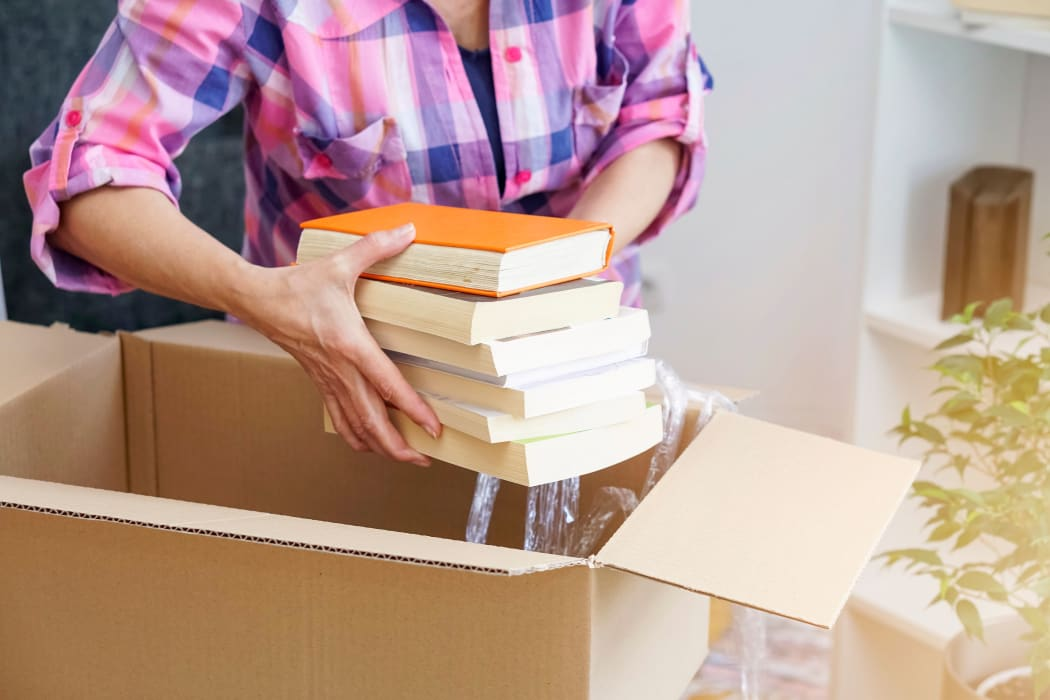 Resident packing books to be stored at Lockaway Storage in San Antonio, Texas