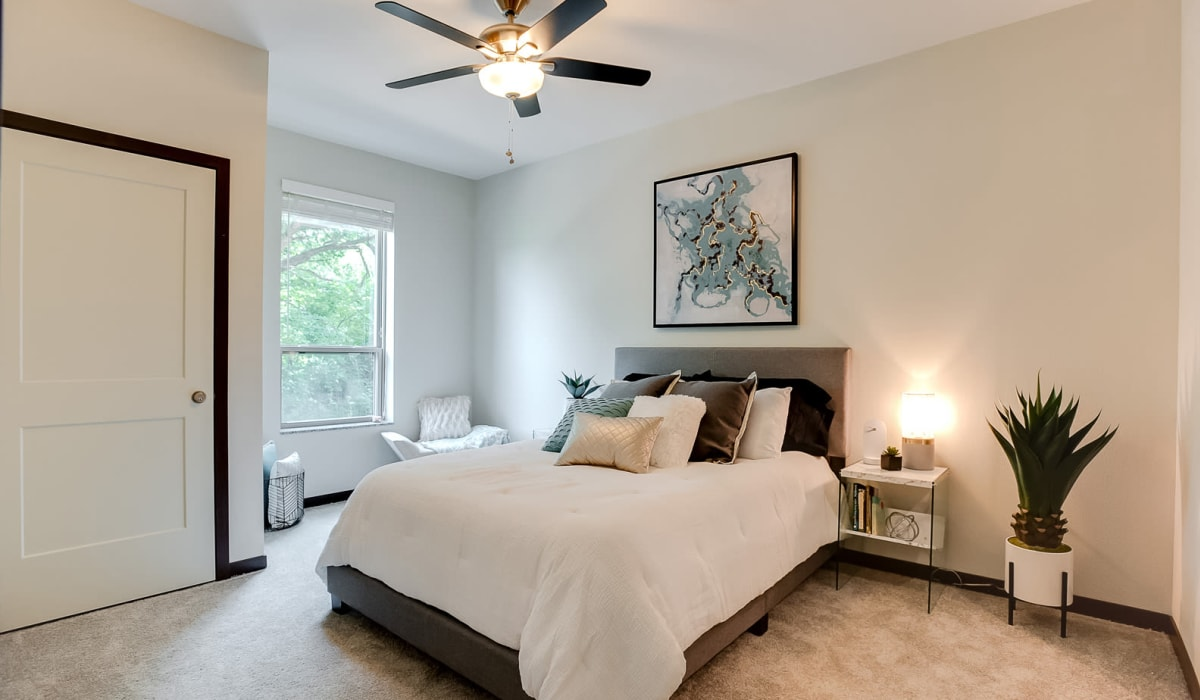 The main bedroom with plush carpeting and a ceiling fan at Lake Jonathan Flats in Chaska, Minnesota