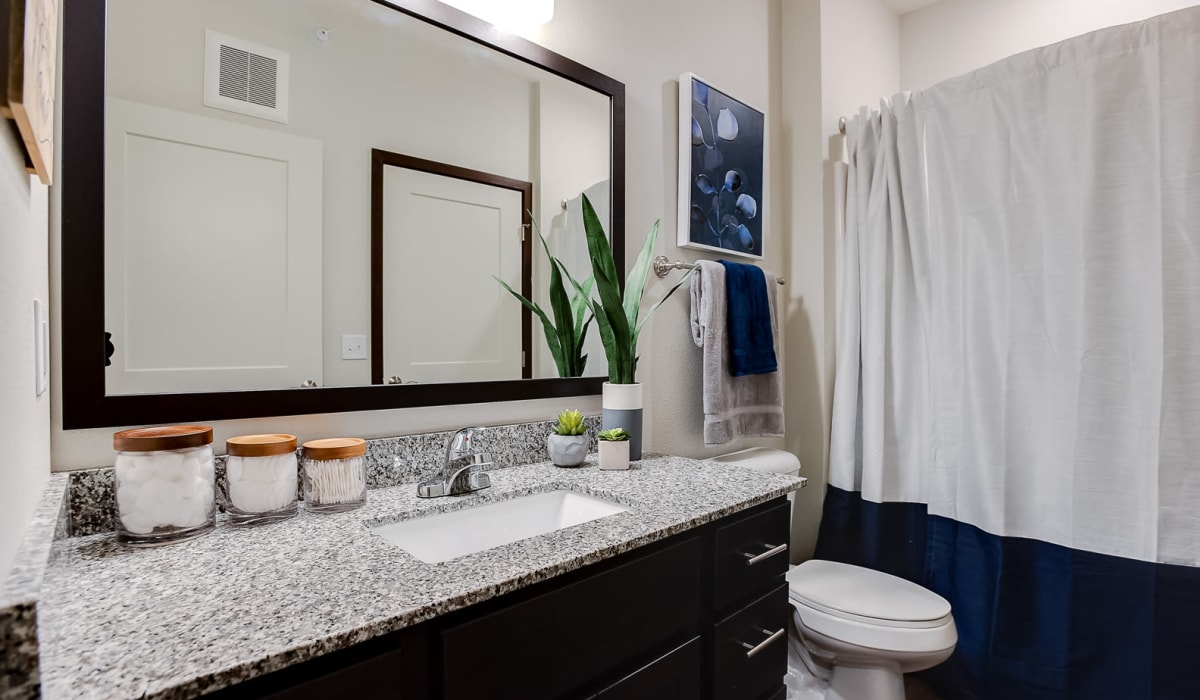 A luxury bathroom with a large vanity mirror at Lake Jonathan Flats in Chaska, Minnesota