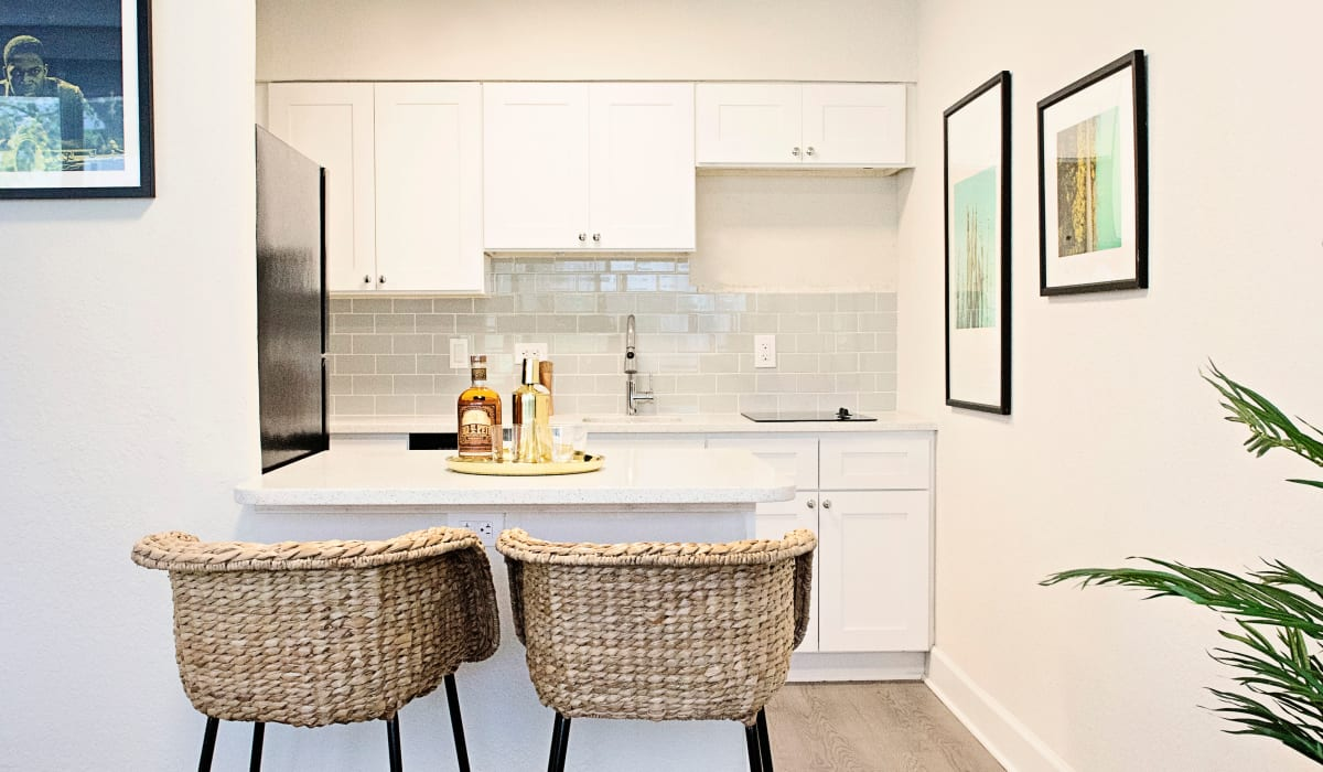 Bright, modern kitchen with white cabinetry and breakfast bar in model home at The Wayland in St Petersburg, Florida