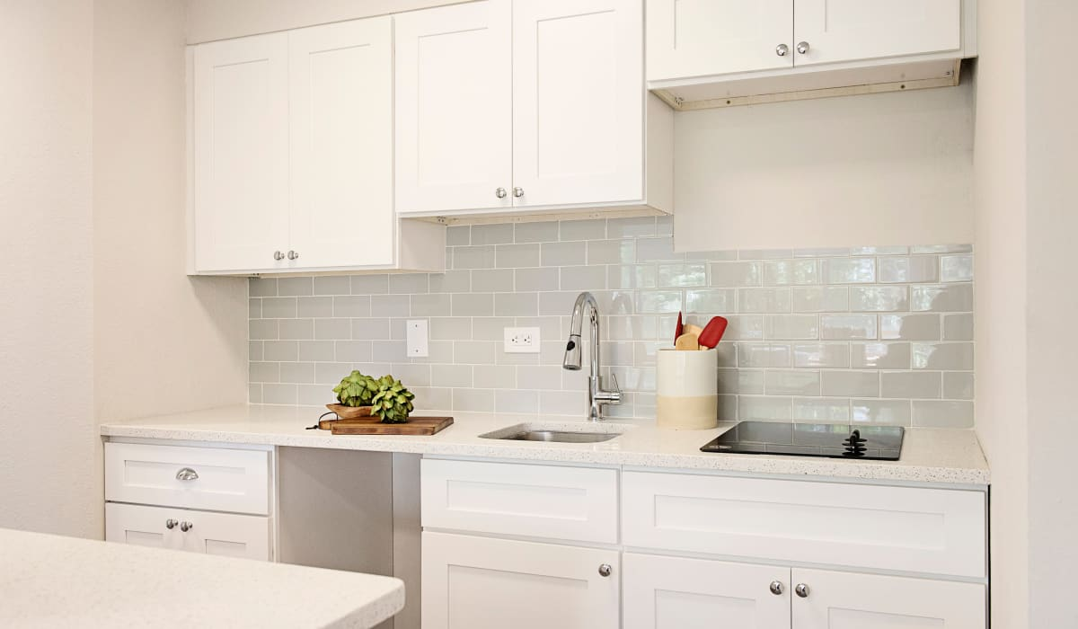 Modern kitchen with subway tile backsplash and white cabinetry and appliances in model home at The Wayland in St Petersburg, Florida