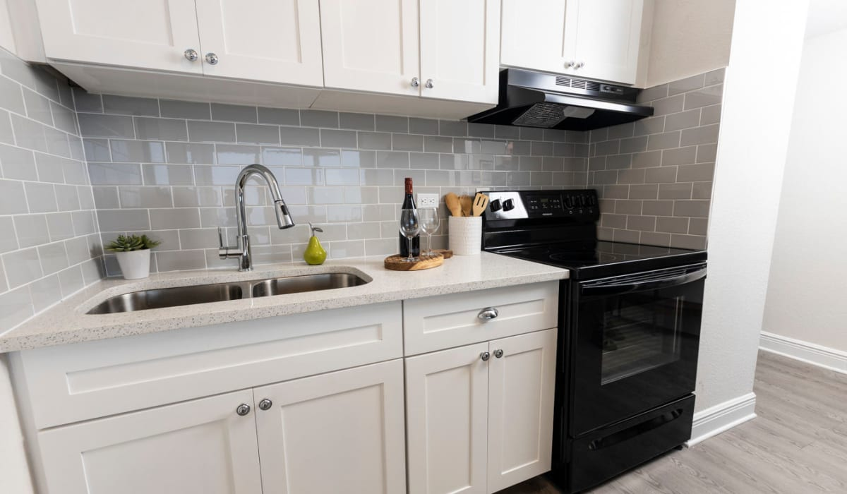 Bright kitchen with white wood cabinets and stainless steel sink at The Wayland in St Petersburg, Florida