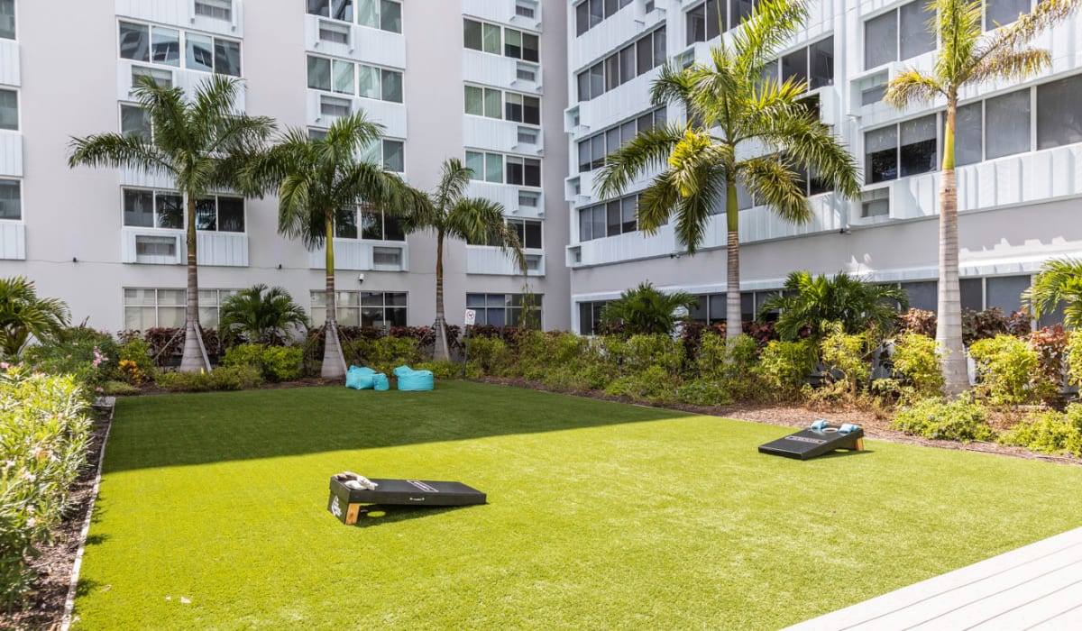 Green lawn space with corn hole for residents at The Wayland in St Petersburg, Florida