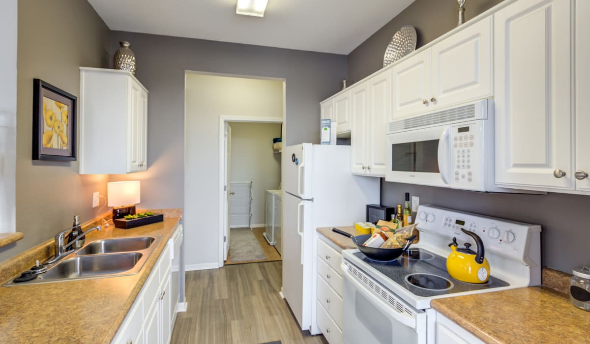 Kitchen with white cabinets and stainless-steel sink at Alvadora Apartments in Lawrence, Kansas