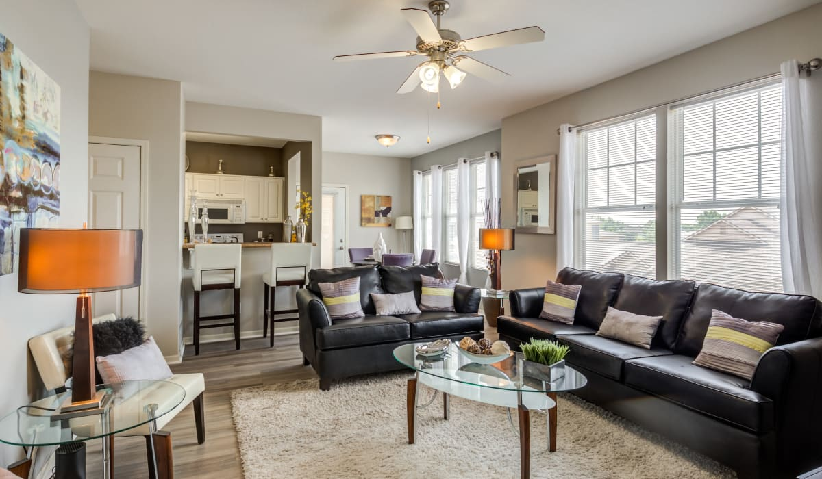 Spacious living room with wood-style flooring and an a ceiling fan at Alvadora Apartments in Lawrence, Kansas