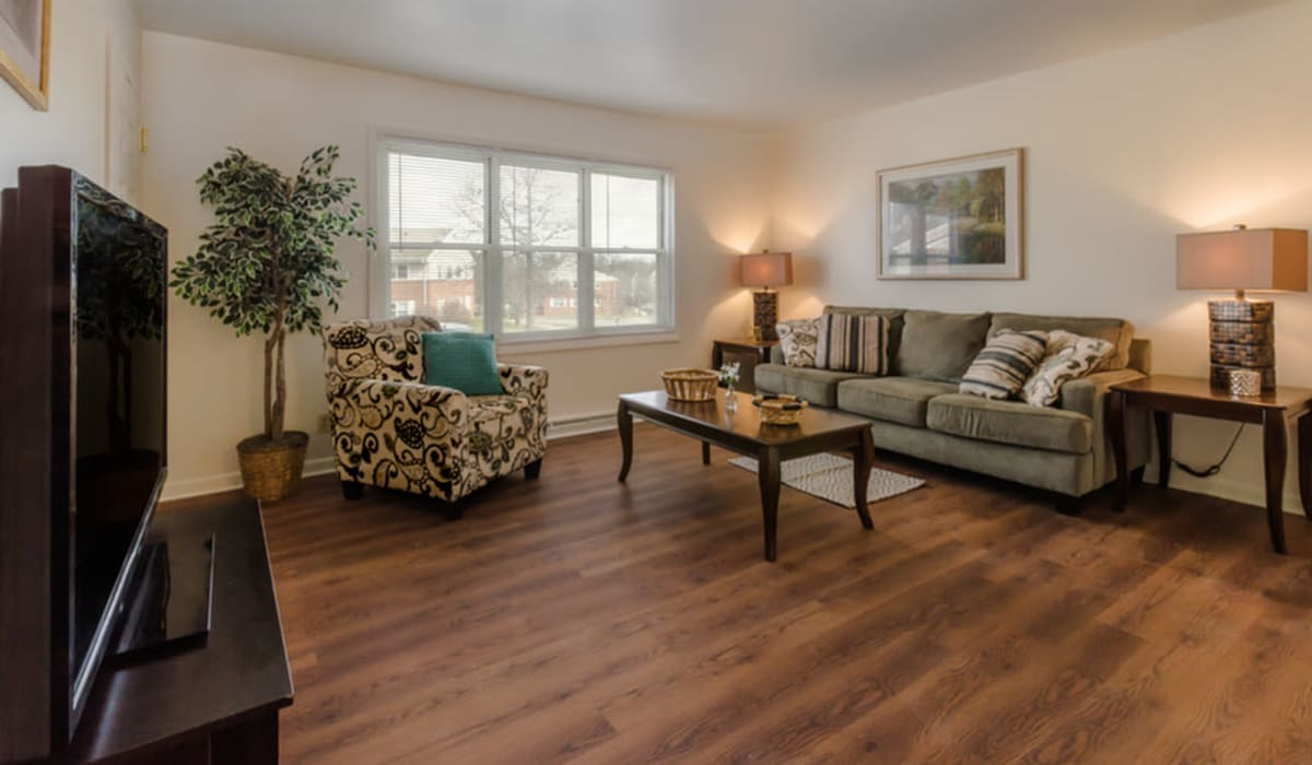 A living room with wood-style flooring at Rochester Highlands in Rochester, New York