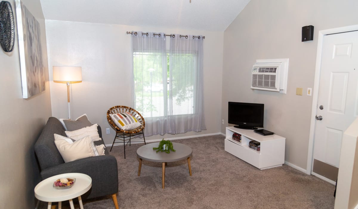 A living room with plush carpeting and a large window at Sunbrook Apartments in Saint Charles, Missouri