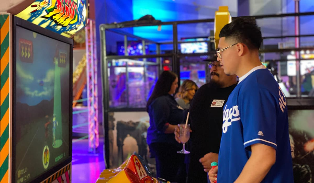 Employees playing games at a company party at Dave & Buster's near E&S Ring Management Corporation in Los Angeles, California