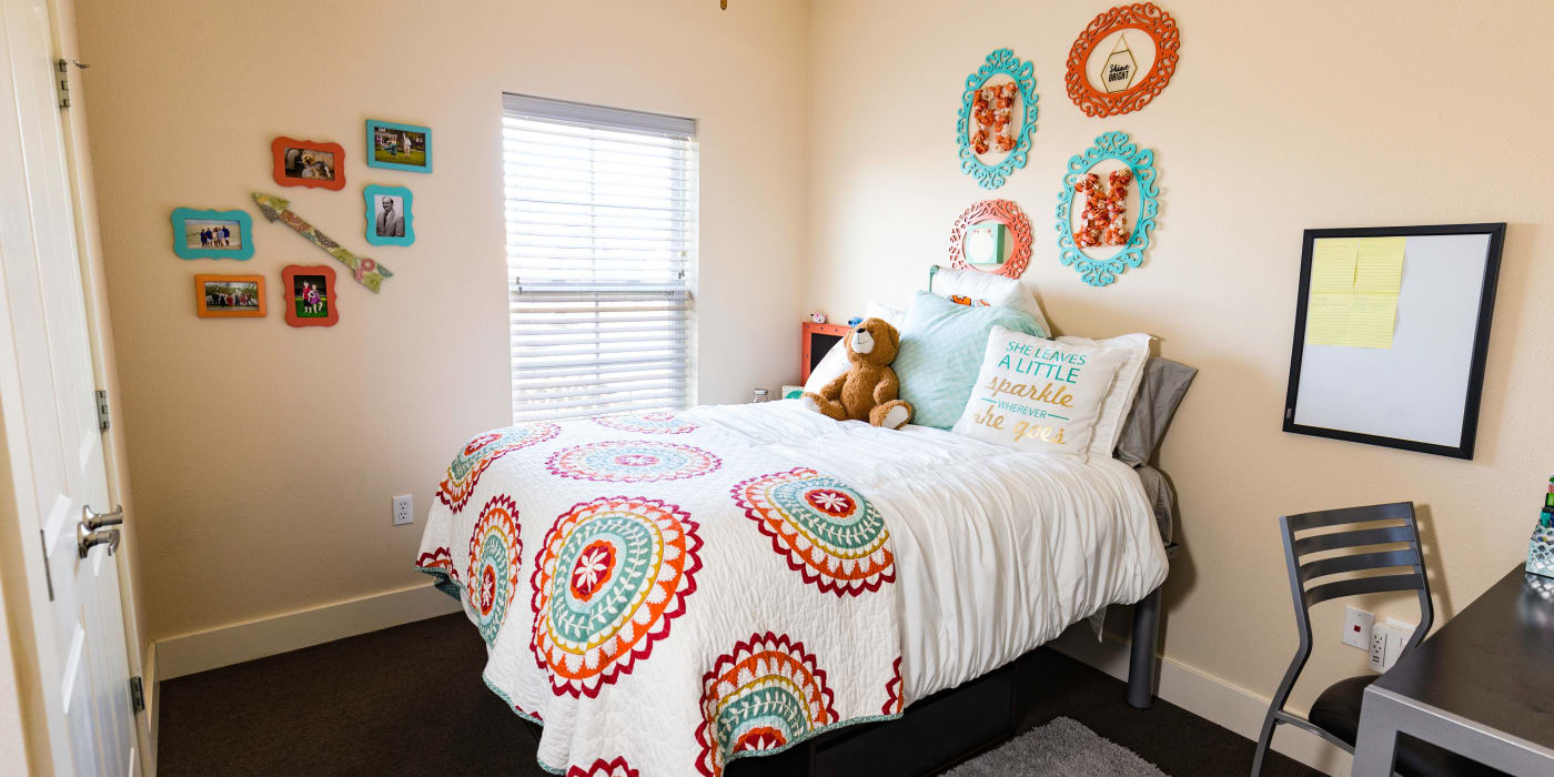 A bedroom with a window and plush carpeting at Beacon Springfield in Springfield, Missouri