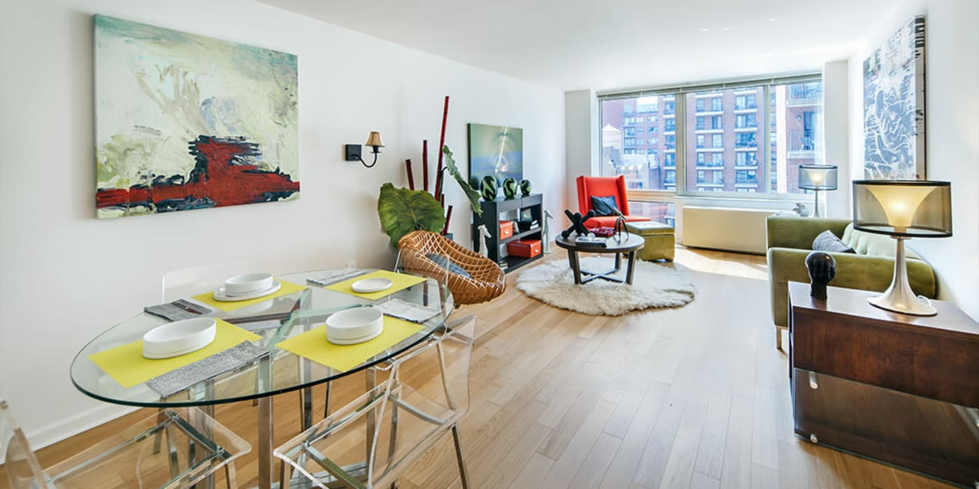 Large windows along the side of the living room overlooking the city at The Ventura in New York, New York