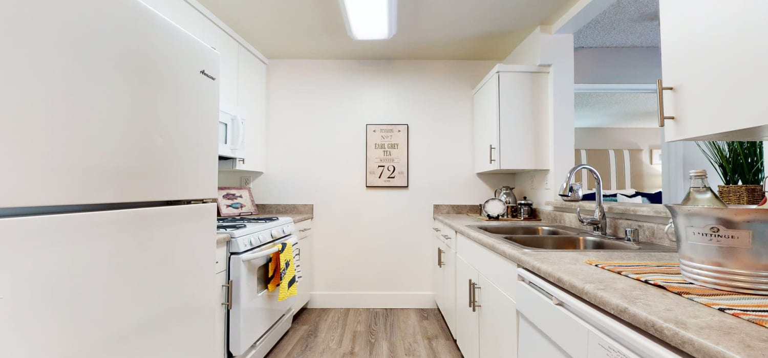 Bright white cabinetry and matching appliances in a model apartment's kitchen at Mountain Vista in Victorville, California