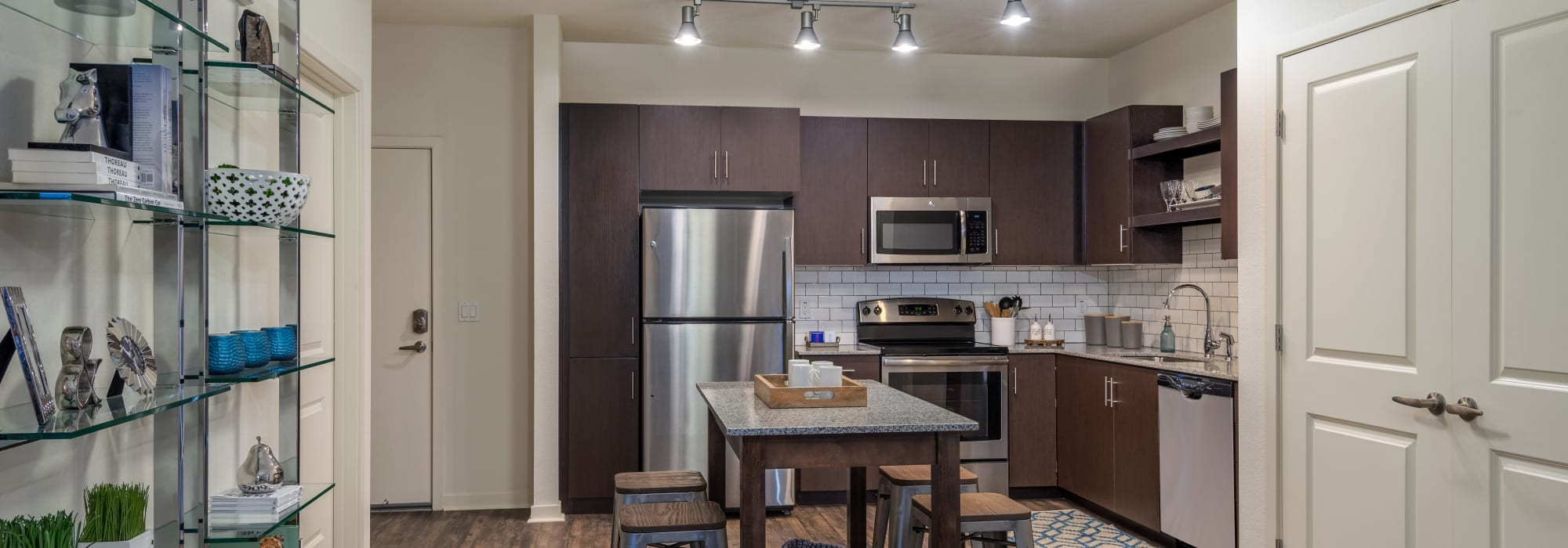 Modern kitchen with dark wood cabinetry in model home at Capital Place in Phoenix, Arizona