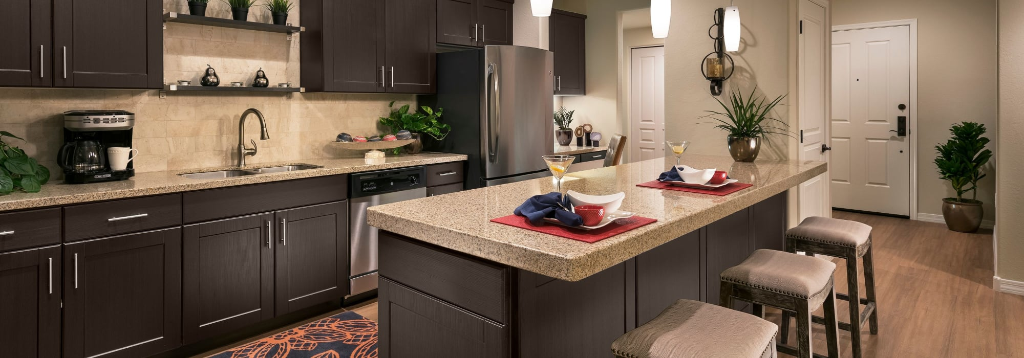 Gourmet kitchen with dark wood cabinetry in model home at San Milan in Phoenix, Arizona