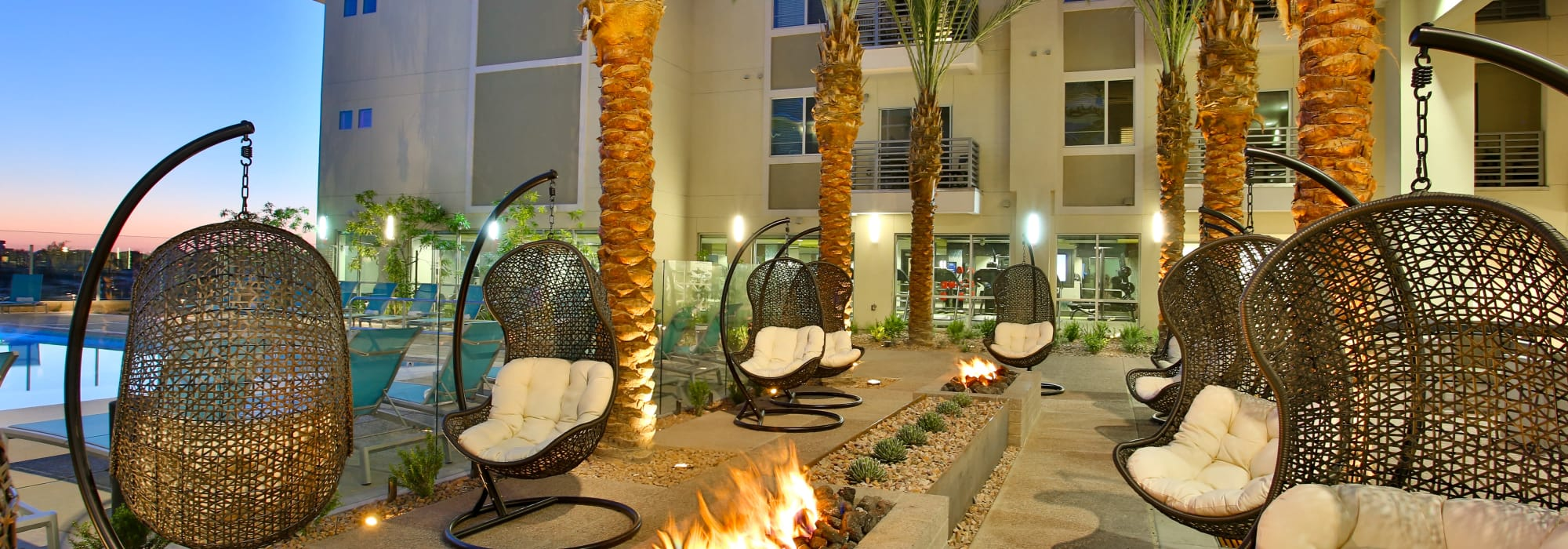 Swinging chairs near the fire pits at dusk at Slate Scottsdale in Phoenix, Arizona