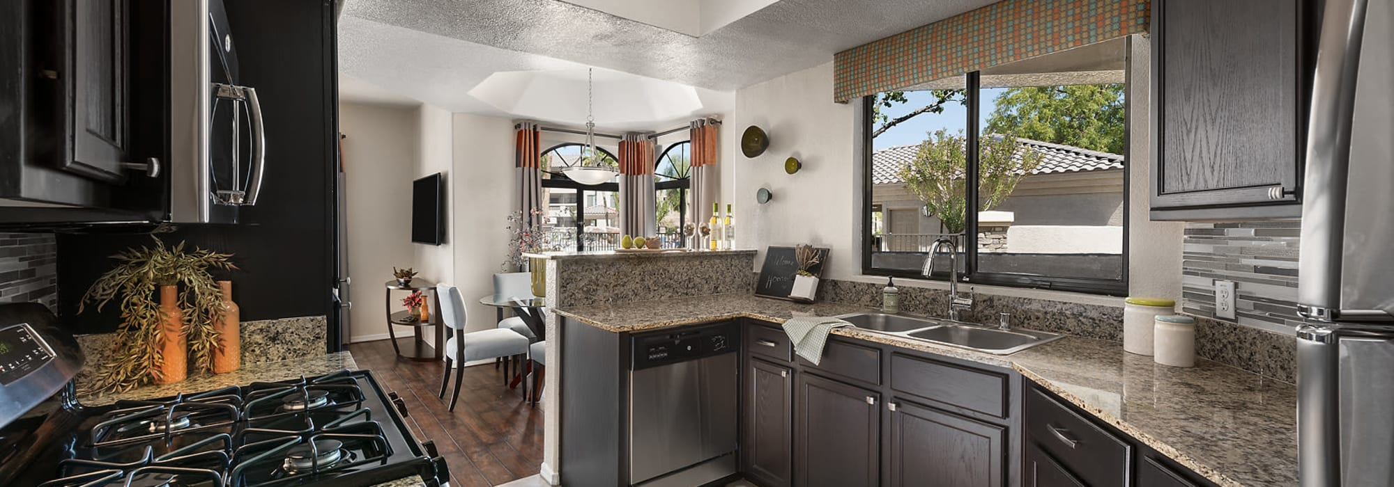 Modern kitchen with black appliances in a model home at San Pedregal in Phoenix, Arizona
