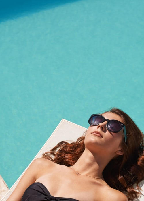 Resident relaxing by the pool at RISE on Chauncey in West Lafayette, Indiana