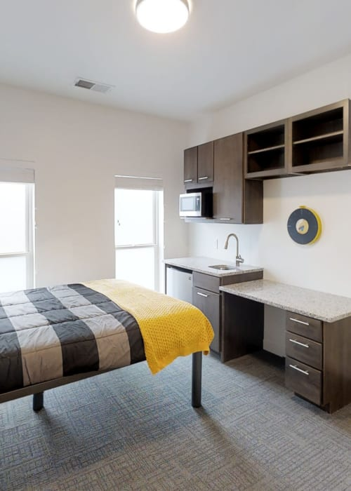 Large bedroom with tons of natural light and small kitchen area at The View on Pavey Square in Columbus, Ohio