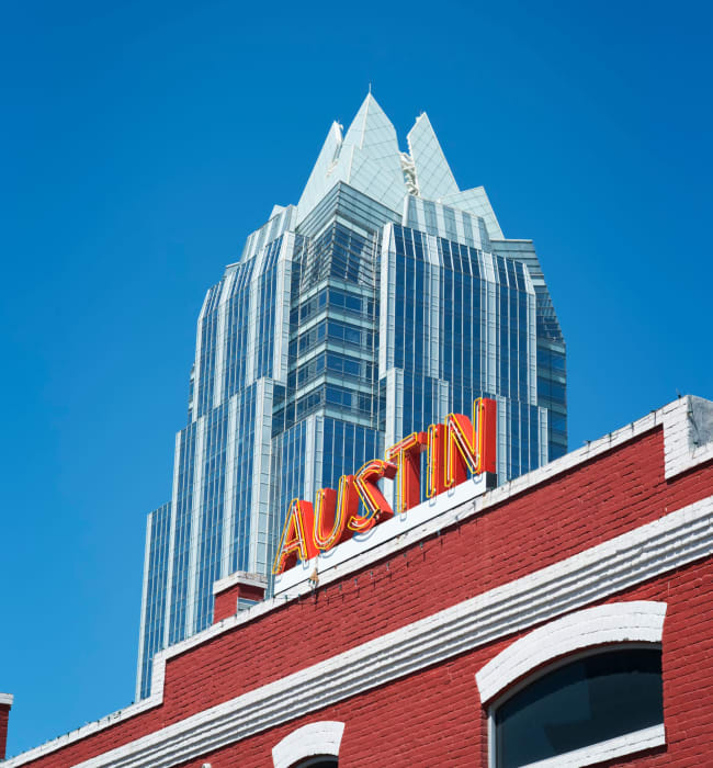 Austin sign on building with skyscraper in background near The 704 in Austin, Texas