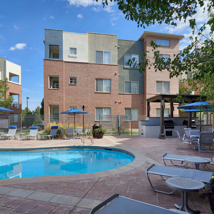 Swimming pool view with lounges and covered BBQ area at The Rail at Inverness in Englewood