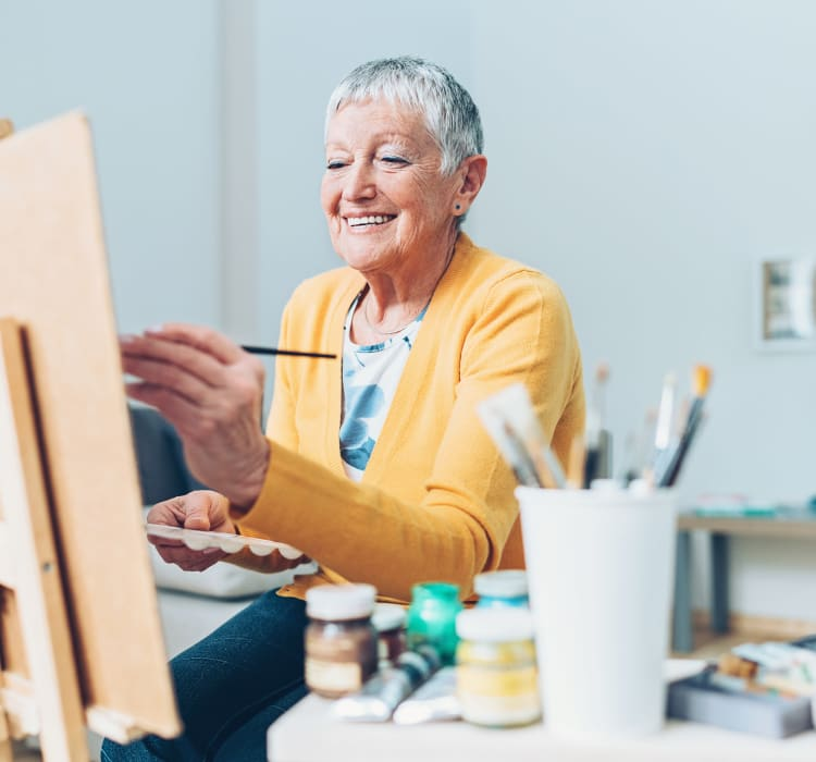 Woman painting at Avenir Memory Care Westside in Los Angeles, California.