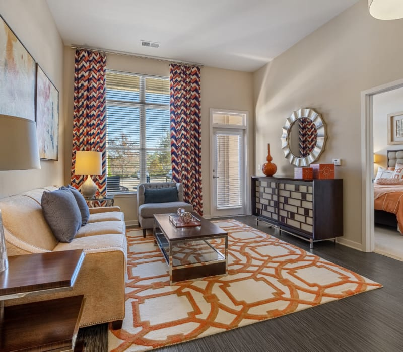 Bright living room with wood flooring and access to private balcony at Marq at Crabtree in Raleigh, North Carolina
