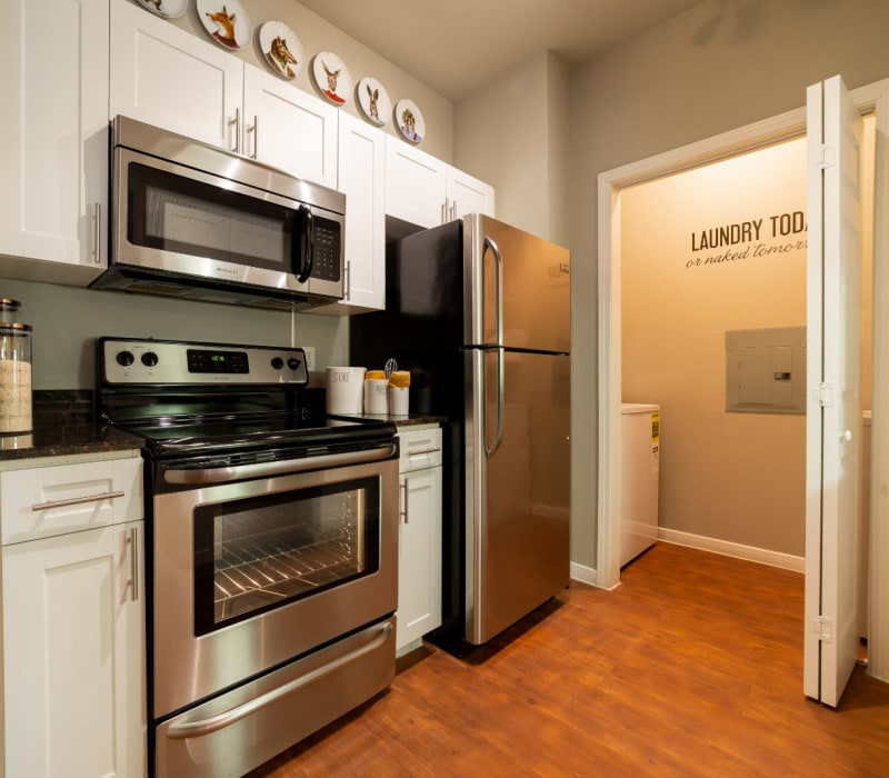 Kitchen with stainless steel appliances and laundry closet at Marquis at Texas Street in Dallas, Texas