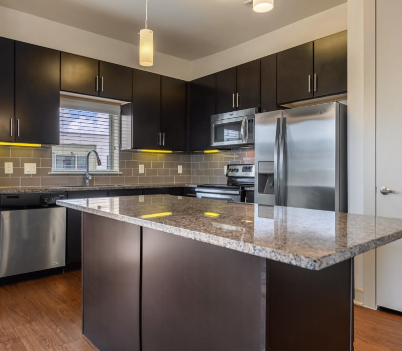 Modern style kitchen with stainless steel appliances and granite countertops at Sabina in Austin, Texas